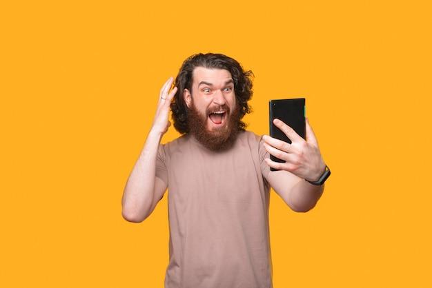 タブレットを見てショックを受けている驚いたひげを生やした男