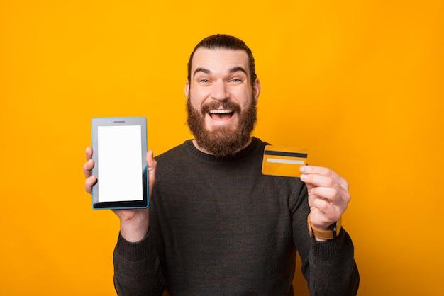 신용 카드와 태블릿 빈 화면을 보여주는 놀된 수염 된 남자
