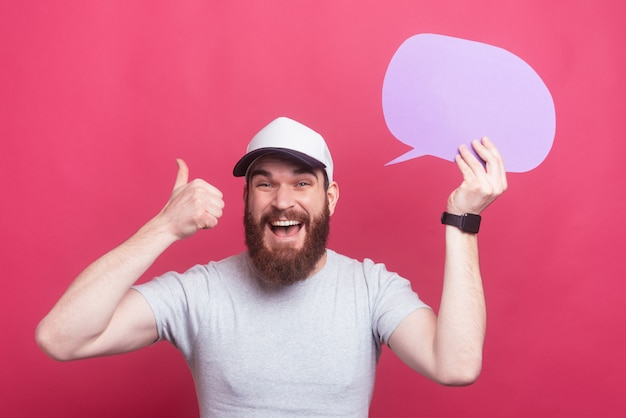 Amazed bearded man showing thumbs up and holding speech bubble