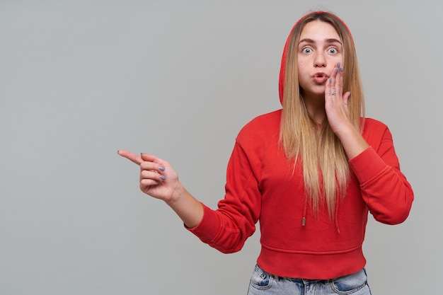 Amazed beautiful blonde young woman with freckles in red hoodie keeps hand on cheek and pointing away to copyspace over gray wall