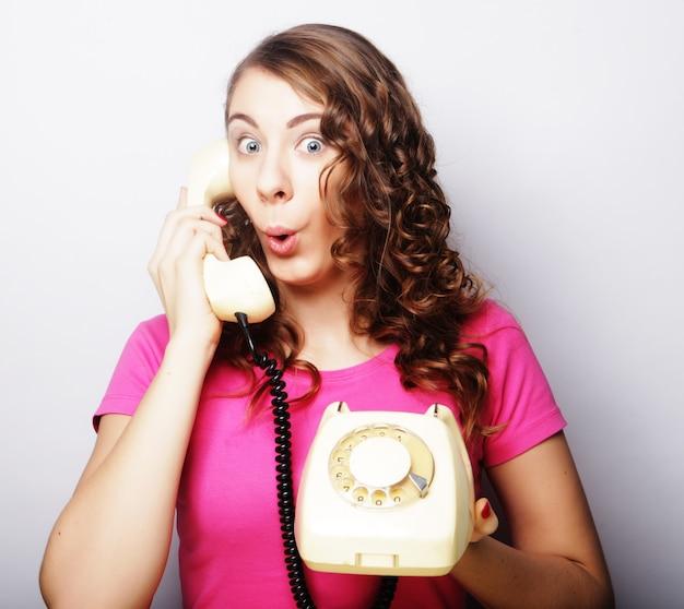 흰색 배경 위에 격리된 흰색 빈티지 전화 통화를 하는 아름다운 곱슬머리 여성
