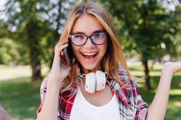 暖かい春の日に電話で話している驚いた美しい少女。自然の中でスマートフォンでポーズをとる眼鏡のジョクンド白人女性。