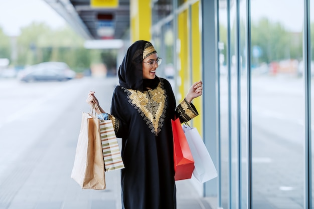 Amazed beautiful muslim woman in traditional wear standing outdoors with shopping bags in hands and looking at shop window.