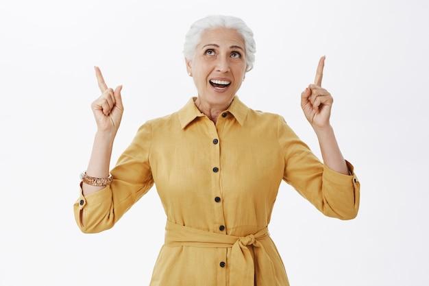 Пораженная красивая старуха смотрит и показывает пальцами вверх
