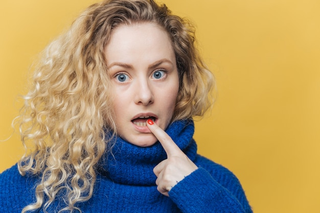 Amazed beautiful woman with curly blonde hair, keeps fore finger on lower lip
