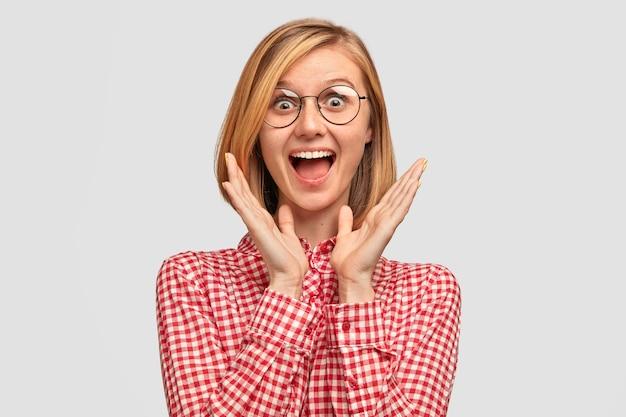 La bella giovane donna europea stupita ha un'espressione gioiosa che nota cosa desiderabile in negozio