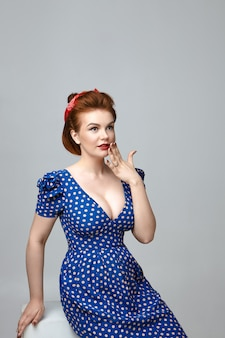 Amazed beautiful young retro model with vintage hairdo and red lipstick holding hand at mouth, expressing full disbelief, surprised with unexpected astonishing news. rockabilly style