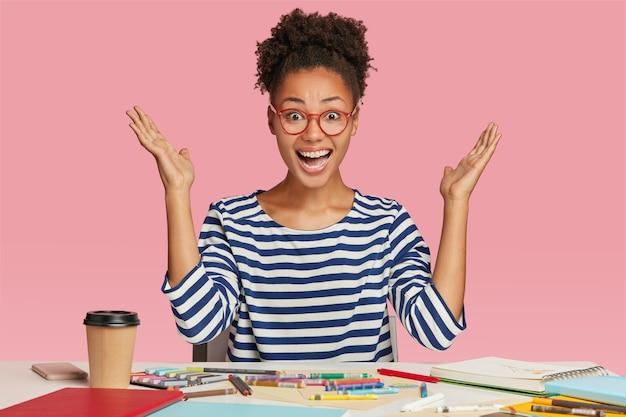 Amazed black female illustrator raises hands in eureka gesture, wears striped clothes