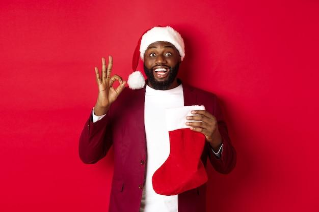 Uomo nero stupito che tiene i regali delle vacanze all'interno del calzino di natale, mostrando il segno ok in approvazione, come qualcosa, in piedi su sfondo rosso