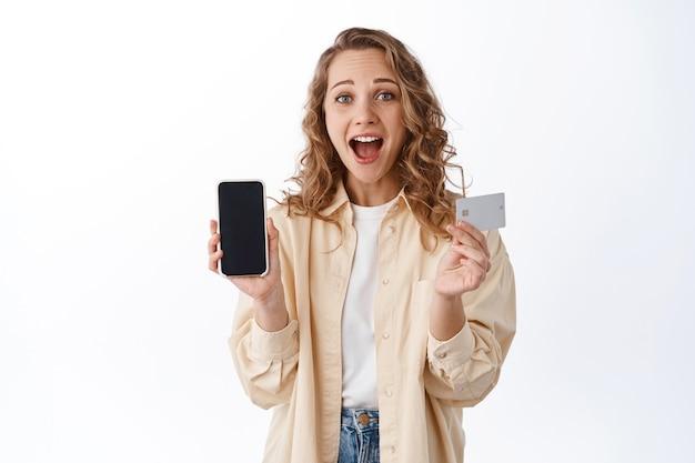 Пораженная блондинка показывает пустой экран смартфона и кредитную карту, говорит, вау, показывает фантастическое предложение, стоя над белой стеной