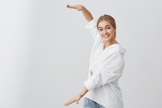 ボックスの長さの手で示す白いシャツで驚かれるブロンドの女の子。きれいな女性が歯に笑みを浮かべてカジュアルな服を着て、大きなもののサイズを示しています。