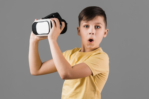 Amazed boy holding virtual reality headset