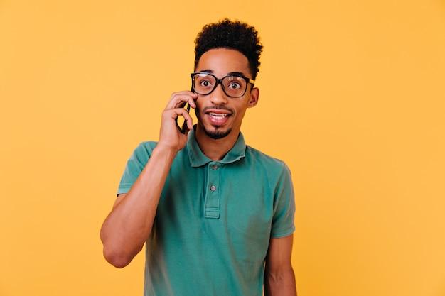 전화 통화하는 큰 안경에 놀란 된 소년입니다. 누군가를 호출하는 녹색 티셔츠에 감정적 인 아프리카 남자의 실내 초상화.