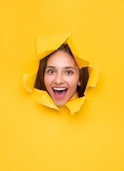 カメラに向かって明るく笑っている破れた黄色い紙のバナーの穴に現れる驚いたブルネット