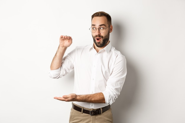 Amazed businessman showing big object, describe something large and looking excited, standing over white background.
