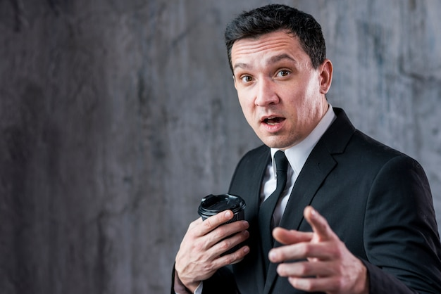 Amazed businessman with coffee cup pointing at camera