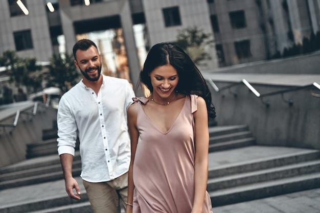 그녀의 아름다움에 놀랐습니다. 그녀의 남자 친구와 함께 도시 거리를 걷는 동안 웃는 아름다운 젊은 여자