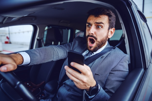 Amazed caucasian businessman in suit driving car and using smart phone at the same time.