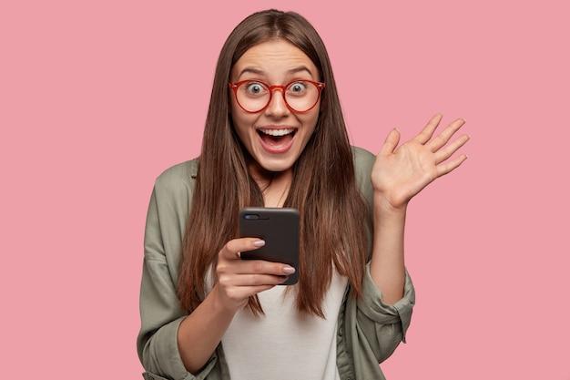La ragazza caucasica stupita tiene il telefono cellulare moderno e mostra la palma