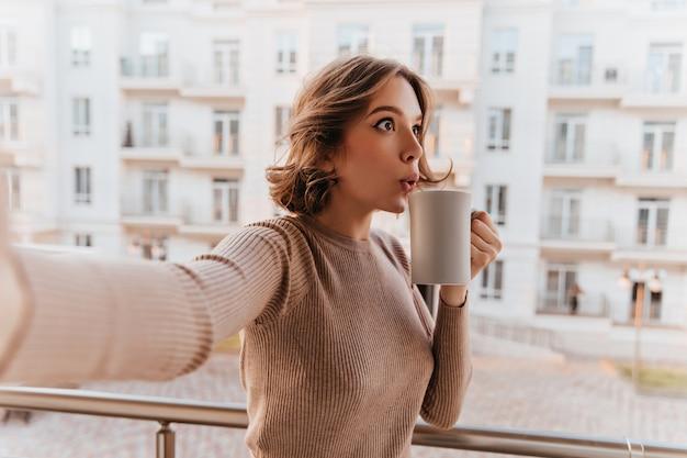 お茶を楽しんでいるスタイリッシュなセーターで驚いた白人女性。一杯のコーヒーを保持し、バルコニーで自分撮りを作る魅力的な巻き毛の女性モデル。