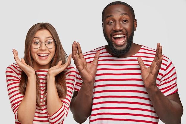 驚いた陽気な多民族の女の子と男は顔の近くで手を握りしめ、気分が良く、幸せを表現し、良い結果を受け取ります