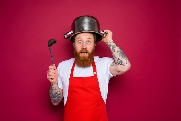Amazed chef with beard and red apron plays with pot