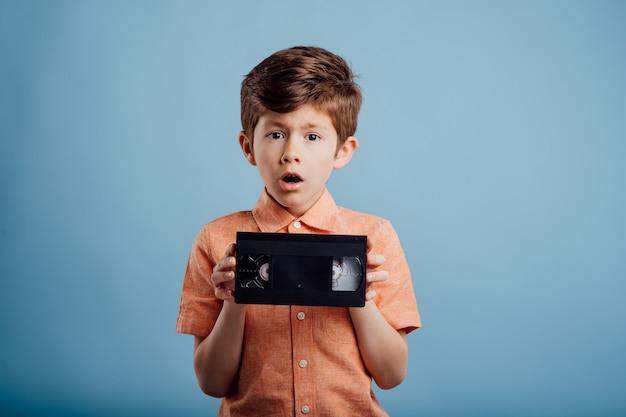 파란색 배경에 격리된 비디오 테이프가 있는 놀란 아이가 카메라를 쳐다본다