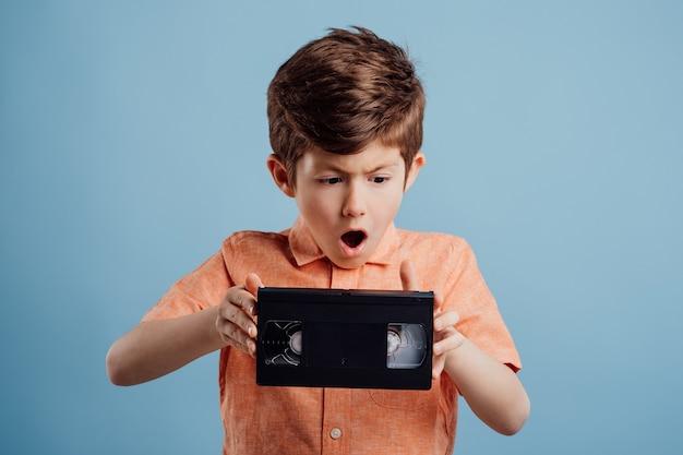 파란색 배경 오래된 가제트에 격리된 비디오 테이프를 가진 놀란 아이