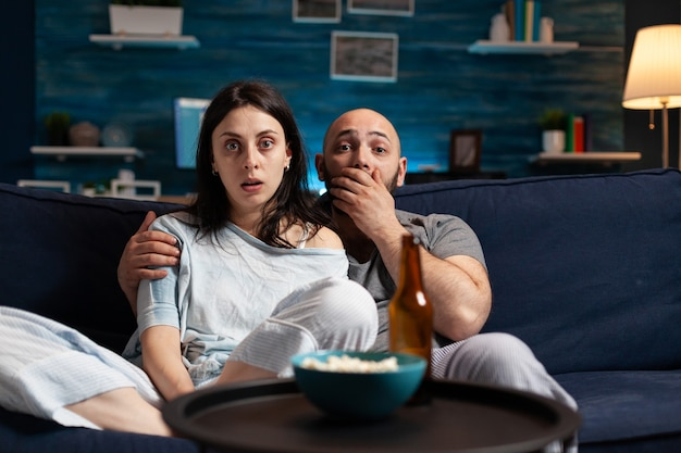Amazed confused couple watching movie on tv at night and eating popcorn