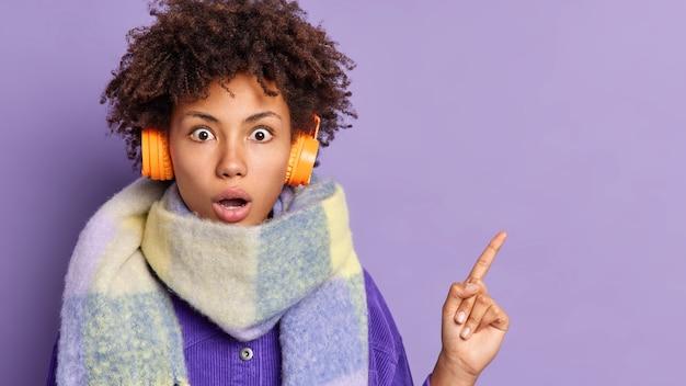 驚いた巻き毛のミレニアル世代の女の子が驚くべきことに、右上隅に何か素晴らしいものを示し、首の周りの耳にステレオヘッドフォンを着用していることを示しています