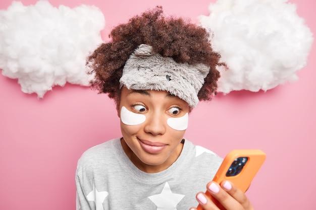 놀란 곱슬 머리 여자는 파자마 옷을 입은 눈 아래에 패치를 적용하고 sleepmask는 스마트 폰을 보유하고 위의 분홍색 벽 흰 구름 위에 고립 된 문자 메시지를 보냅니다.