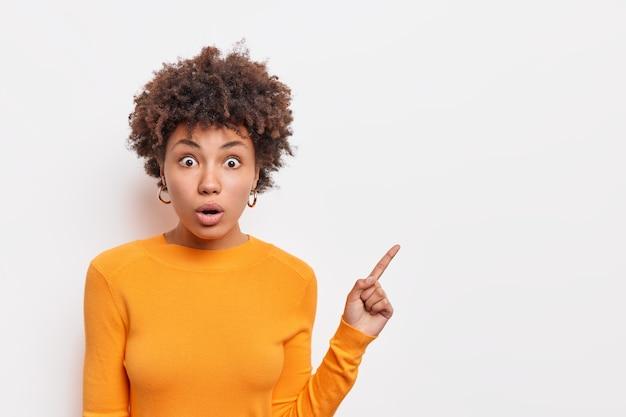 ショックを受けた表情で驚いた巻き毛の若い女性は、白い壁に隔離された空白のスペースにオレンジ色のジャンパーポイントを脇に置いて驚いた表情をしています。広告用のコピースペース