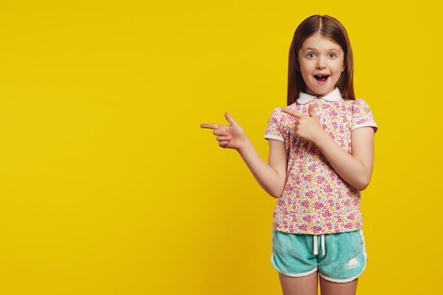 Пораженная милая девочка показывает пальцами в сторону, показывая пустое пространство