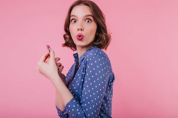 Amazed cute lady with trendy hairstyle doing her makeup on bright pink wall. glamorous girl in stylish blouse holding lipstick.