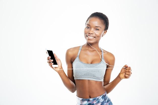 휴대 전화에서 음악을 듣고 놀란 귀여운 젊은 아프리카 계 미국인 sportswoman