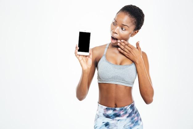 Пораженная милая молодая афро-американская спортсменка, глядя на пустой экран мобильного телефона на белом фоне