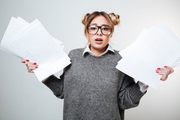 Amazed cute young woman in glasses standing and holding documents
