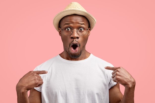 Amazed dark skinned guy points at casual t shirt, shows free space for your advertising content