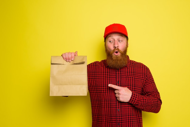 Amazed delivery man with hat and beard