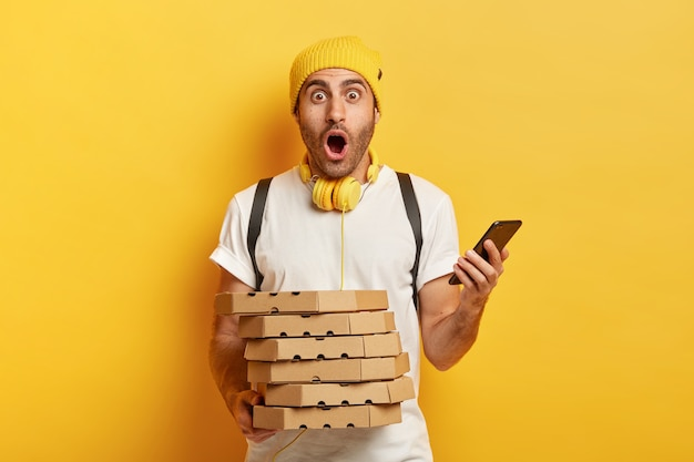 Amazed deliveryman receives orders from customers via smartphone, holds pile of cardboard pizza boxes, carries rucksack, wears hat and t shirt, isolated over yellow background, works in restaurant