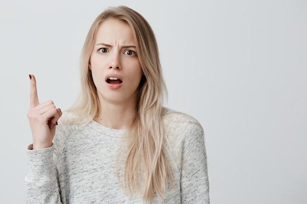 Пораженная неудовлетворенная женщина с окрашенными светлыми волосами, одетая небрежно, указательным пальцем вверх в шоке. недовольная женщина, указывающая что-то над головой