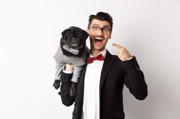 Пораженный владелец собаки, указывая на своего милого черного мопса, счастливый улыбающийся, щенок в белом костюме.