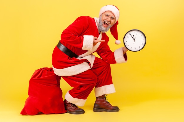 Amazed elderly man with gray beard in santa claus costume sitting on big red bag with presents for christmas, pointing at wall clock with excitement. indoor studio shot isolated on yellow background.