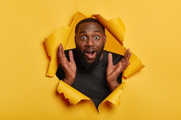 Amazed emotional afro american man raises hands up, stares with surprised expression, gasps from wonder, being unshaven, clasps palms, poses through hole in yellow paper