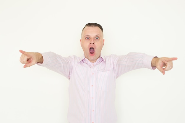 Amazed emotional man pointing at camera and screaming.