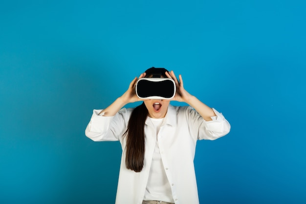 Amazed emotional woman wearing virtual reality goggles experiencing 3d gadget and standing on blue