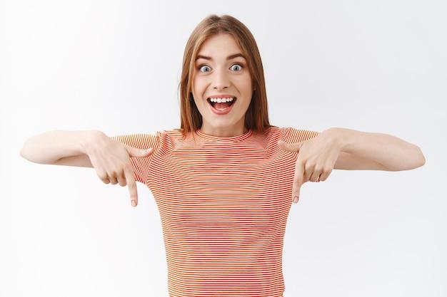Пораженная, восторженная красивая женщина в полосатой футболке, задыхающаяся от счастья и удивления, видит невероятные крутые вещи, показывает пальцем вниз, обращает внимание на крутое промо, белый фон