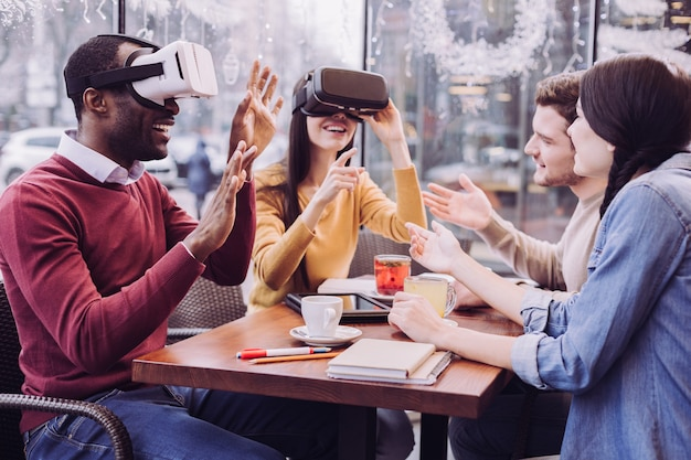 Amazed enthusiastic two friends sitting in vr headsets while laughing and spending time with friends