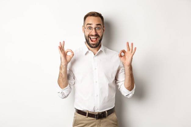 Imprenditore stupito che mostra il segno giusto e sembra felice, soddisfatto del prodotto, in piedi bianco