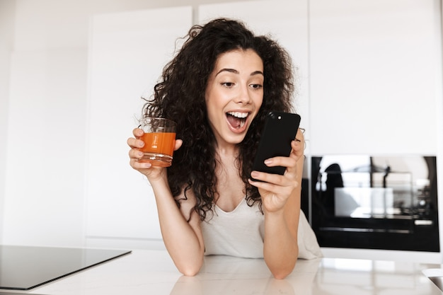 Изумленная европейская женщина 20 лет с вьющимися волосами в шелковой одежде для отдыха пьет сок на кухне, пользуется черным мобильным телефоном и выражает волнение.